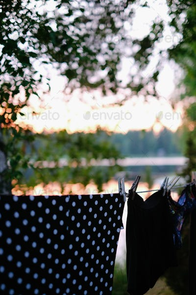 Clothes hanging on drying line near a lake