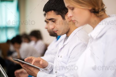 Medical student working with pad on the conference