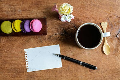 colorful macaroons with coffee and blank note on wooden table