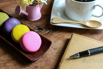 Colorful macaroons and a cup of coffee with notebook