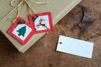Vintage gift box with blank tag on old wooden background, Christmas concept
