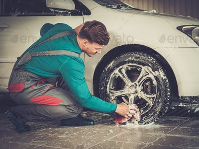 Man worker washing car's alloy rims on a car wash