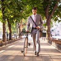 Pensive businessman walking with bicycle
