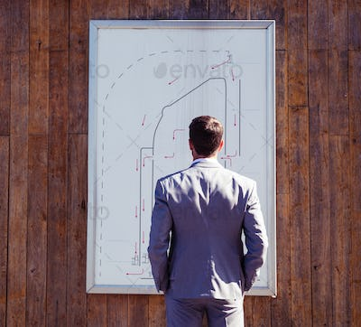 Businessman looking on parking booth plan