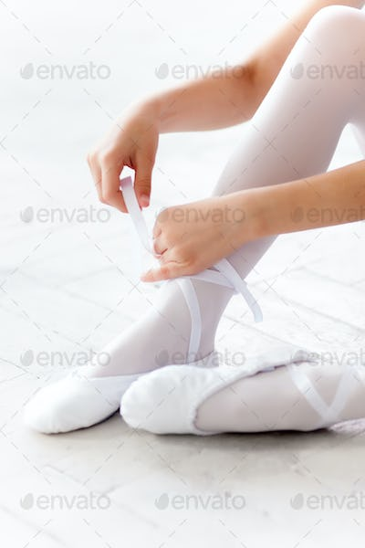 little ballerina puting on foot pointe shoes