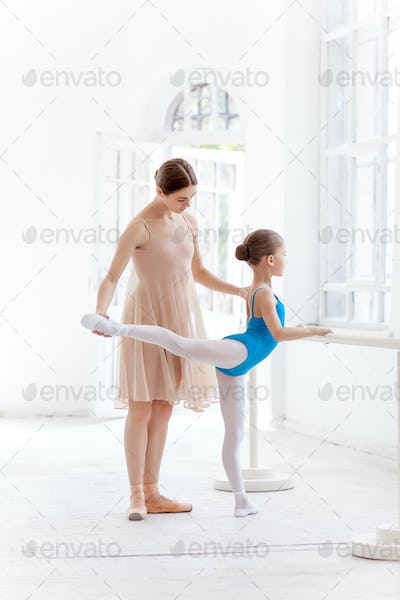 The little ballerina posing at ballet barre with personal teacher in dance studio