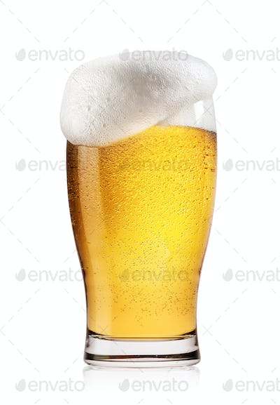 Glass of light beer with white foam