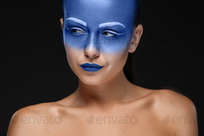 Portrait of a woman who is posing covered with blue paint