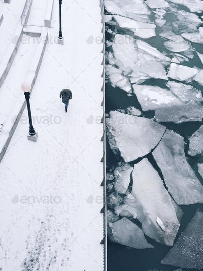 A Man Walking Along The River with Ice Flows in the Winter