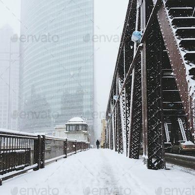 A Man Walking on a Bridge In Snowstorm