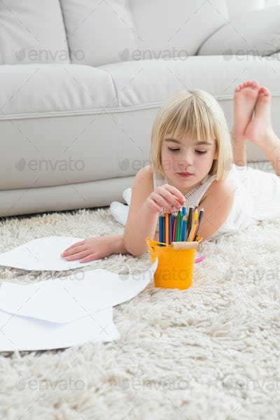 Smiling litlle girl drawing lying on the floor at home in the living room
