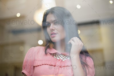 Pretty brunette smiling and thinking seen through window