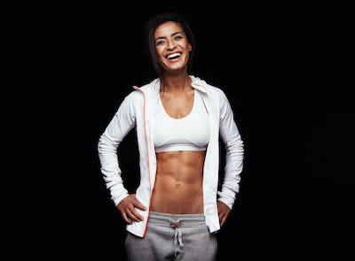 Smiling sportswoman on black background