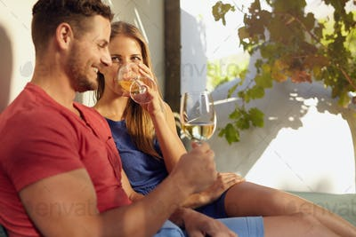 Young couple relaxing outdoors drinking wine