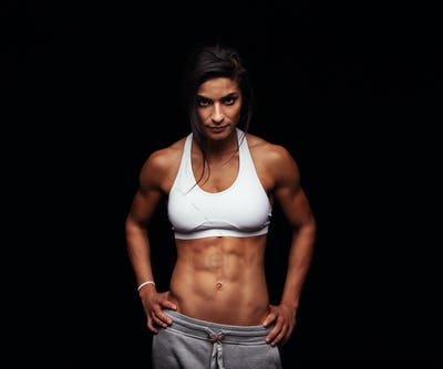 Fitness female model posing on black background