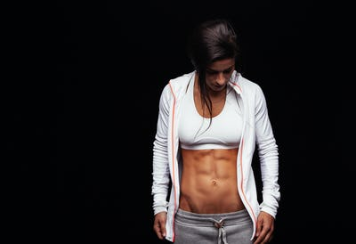 Woman with perfect abdomen muscles in sportswear