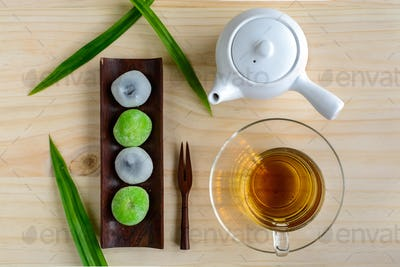 Daifuku green tea and sesame filling with cup of tea on wooden table