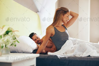 Attractive woman waking up in morning with her husband sleeping