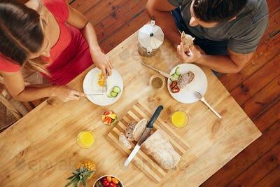 Couple enjoying a healthy morning breakfast in kitchen
