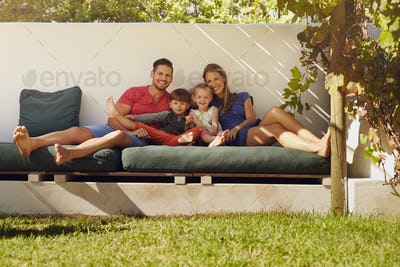 Happy young family sitting on patio