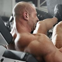 bodybuilder working out at the gym while using fitness machine