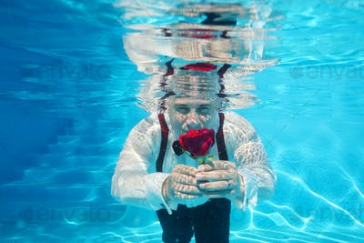 underwater groom with red rose