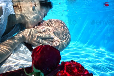 bride and groom kissing underwater