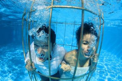 bride and groom underwater