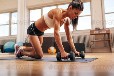 Powerful woman doing push-ups on dumbbells