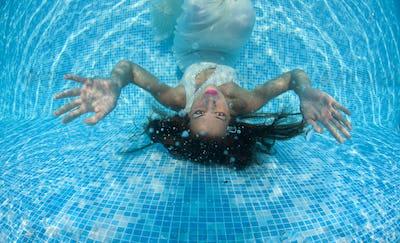 Beautiful woman girl dress underwater diving swim blue sunny day pool