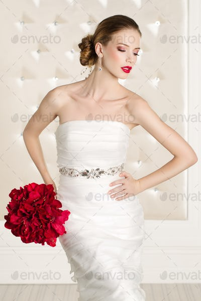 Gorgeous bride with white dress with red flowers bouquet