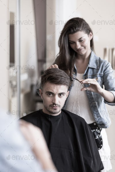 Young hairdresser and male customer