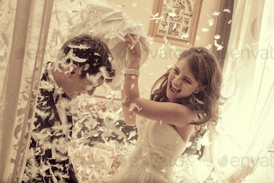 bride and groom fighting with pillows