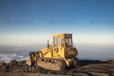 Yellow tractor at the top of the Etna mountain with view on the clouds
