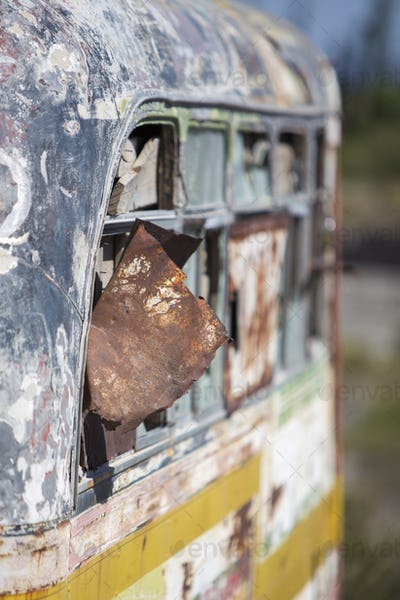 Rusted out old school bus abandoned in the countryside