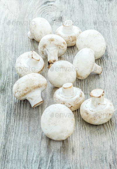 The champignons on wooden background