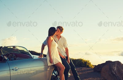 Couple Watching the Sunset and Kissing with Classic Vintage Car