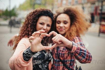Friends making heart shape with fingers