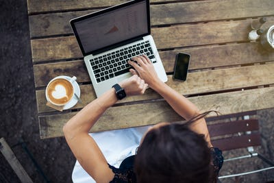Woman at coffee shop checking time on smartwatch