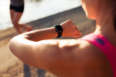 Runner checking time on her smartwatch