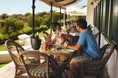 Young couple enjoying a glass of wine at winery restaurant