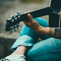 Man with tattoes playing guitar