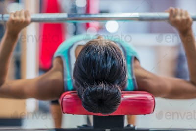 Woman workout with barbell on the bench