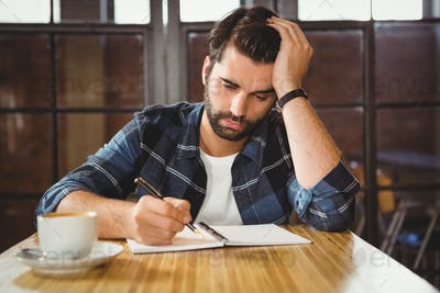 Young man taking notes in his notebook at a cafe