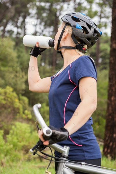 Athletic blonde drinking and holding mountain bike in the nature