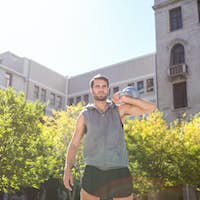 Handsome athlete holding kettle bell in the city