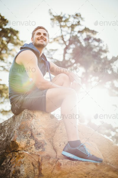 Young happy jogger sitting on rock and looking away in the nature