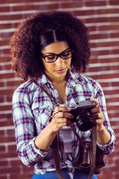 Attractive hipster looking at photos on camera against red brick background