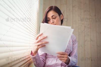 Pretty brunette reading documents beside window in a bright room