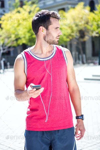 Handsome athlete sending a text while looking away on a sunny day
